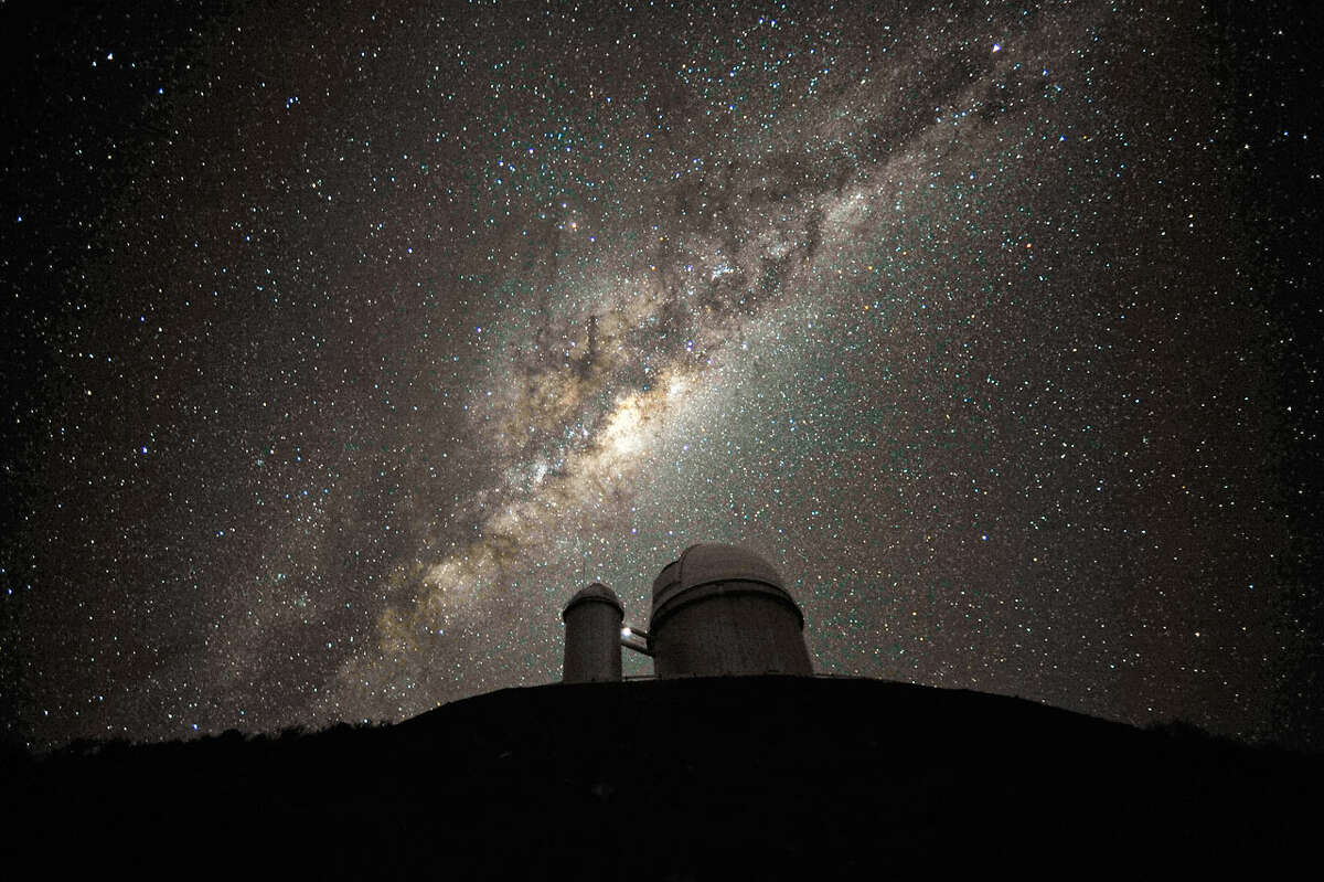 The ESO 3.6-metre telescope at La Silla, during observations. The Milky Way, our own galaxy, stretches across the picture: it is a disc-shaped structure seen perfectly edge-on. Above the telescope´s dome, here lit by the Moon, and partially hidden behind dark dust clouds, is the yellowish and prominent central bulge of the Milky Way.