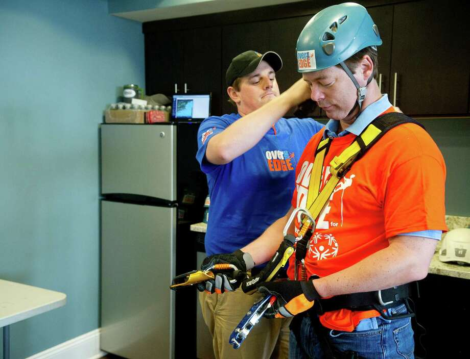 Ryan Kelley, left, helps John Freeman, right, prepare to rappel down 101 Park Place at Harbor Point in Stamford, Conn., during Over the Edge, a fundraiser for Special Olympics Connecticut. Photo: Lindsay Perry / Stamford Advocate