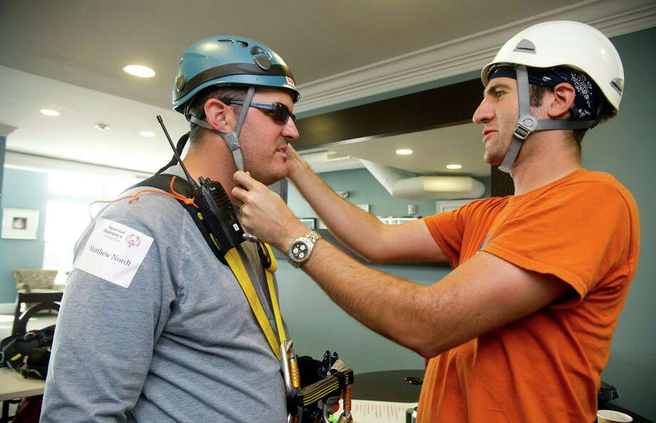 Robert Pitkin, right, helps Matthew Nordt prepare to rappel down 101 Park Place at Harbor Point in Stamford, Conn., during Over the Edge, a fundraiser for Special Olympics Connecticut. Photo: Lindsay Perry / Stamford Advocate