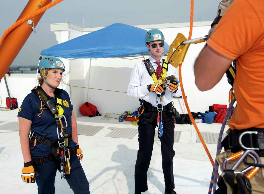 Diane Maclean, left, and James Wilcox, right, get a lesson in rappelling before decending down 101 Park Place at Harbor Point in Stamford, Conn., during Over the Edge, a fundraiser for Special Olympics Connecticut. Photo: Lindsay Perry / Stamford Advocate