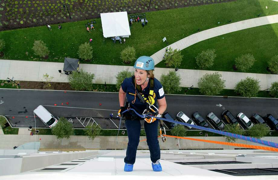 Diane Maclean rappels down 101 Park Place at Harbor Point in Stamford, Conn., during Over the Edge, a fundraiser for Special Olympics Connecticut. Photo: Lindsay Perry / Stamford Advocate