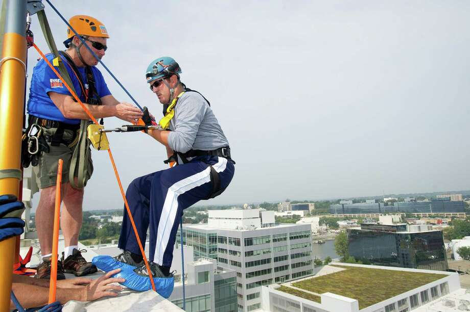 Matthew Nordt rappels down 101 Park Place at Harbor Point in Stamford, Conn., during Over the Edge, a fundraiser for Special Olympics Connecticut. Photo: Lindsay Perry / Stamford Advocate