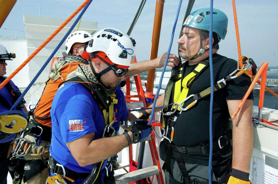 John Clapps rappels down 101 Park Place at Harbor Point in Stamford, Conn., during Over the Edge, a fundraiser for Special Olympics Connecticut. Photo: Lindsay Perry / Stamford Advocate