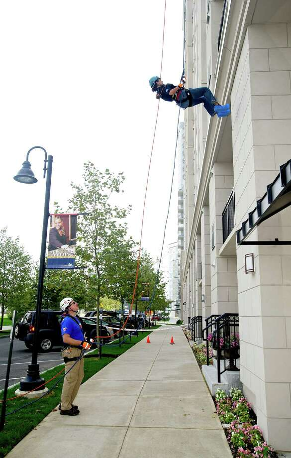 Lynn Souza rappels down 101 Park Place at Harbor Point in Stamford, Conn., during Over the Edge, a fundraiser for Special Olympics Connecticut. Photo: Lindsay Perry / Stamford Advocate