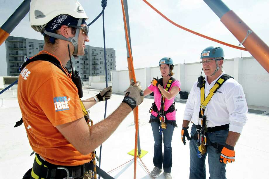 Robert Pitkin, left, gives Maureen Pienta and Al Barbarotta a lesson in rappelling before they descend 101 Park Place at Harbor Point in Stamford, Conn., during Over the Edge, a fundraiser for Special Olympics Connecticut. Photo: Lindsay Perry / Stamford Advocate