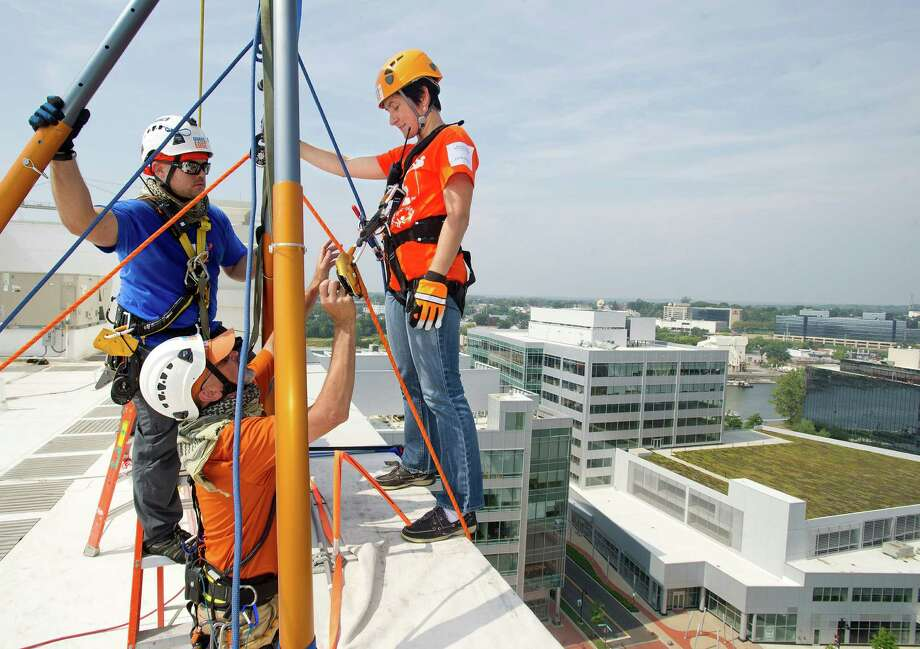 Elena Moffly rappels down 101 Park Place at Harbor Point in Stamford, Conn., during Over the Edge, a fundraiser for Special Olympics Connecticut. Photo: Lindsay Perry / Stamford Advocate