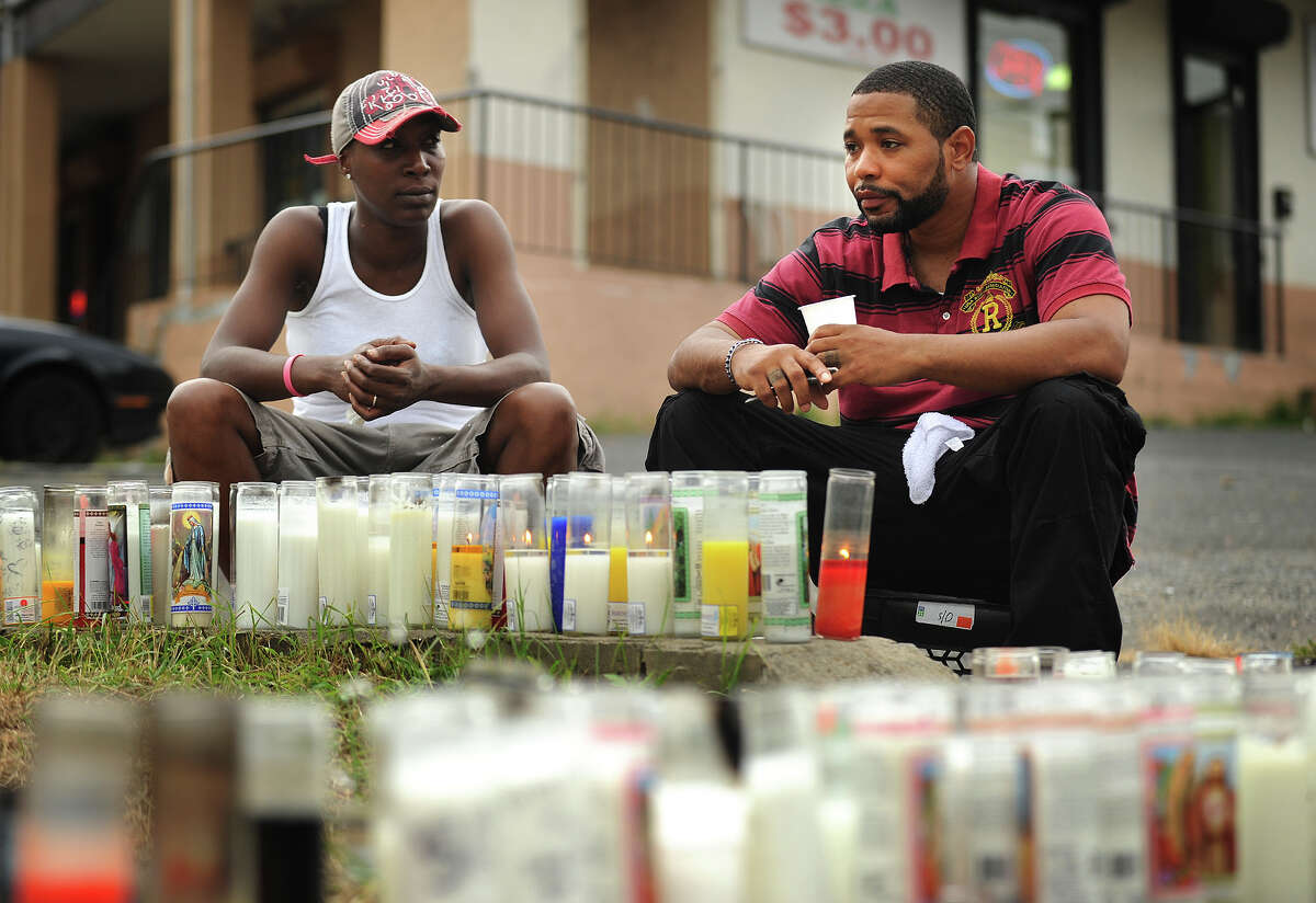 """A woman who identified herself as """"Blaze"""", left, cousin of Christopher Pettway, and an unidentified man, sit by a memorial to Pettway who was gunned down on Tuesday afternoon at the intersection of Reservoir and Trumbull Avenues in Bridgeport, Conn."""