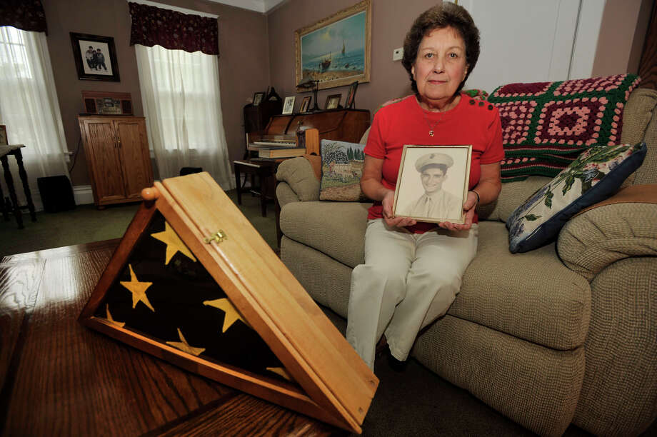 Gloria Battinelli holds a photograph of her brother, Pfc. Oswald Fabrizio, in her home in Stamford, Conn., on Thursday, Sept. 12, 2013. Pfc. Fabrizio died in combat during World War II on Okinawa in 1945. Battinelli has been struggling to get her brother's remains moved from a cemetery in Darien to Arlington National Cemetery and this Saturday, she will get that wish fulfilled. Photo: Jason Rearick / Stamford Advocate