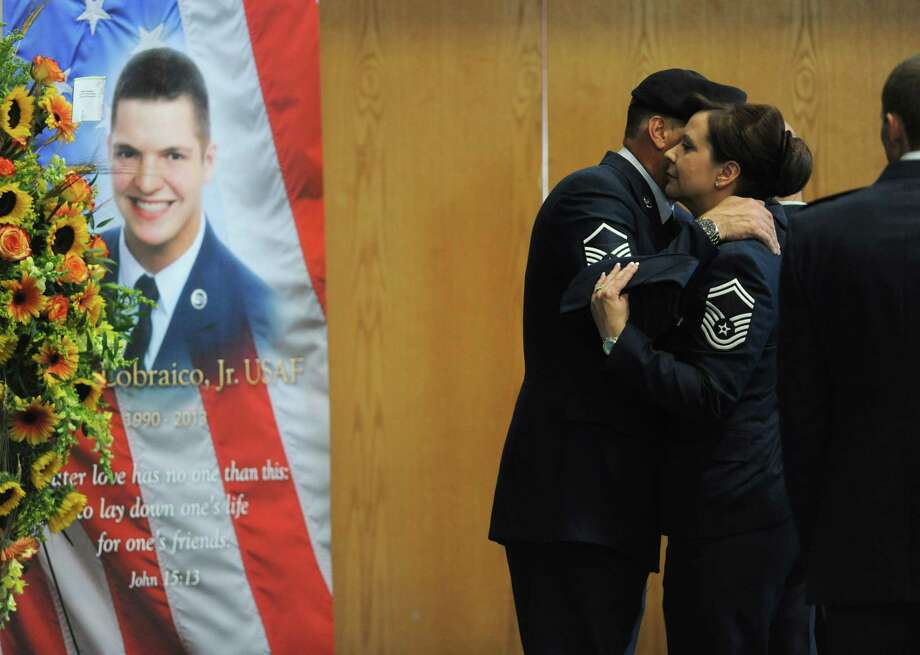 Air National Guard members embrace before heading into the viewing of soldier TJ Lobraico at the O'Neill Center in Danbury, Conn. on Thursday, Sept. 12, 2013.  Staff Sgt. Lobraico, a member of the Air National Guard 105th Security Forces Squadron, was killed last Thursday after his unit was attacked near Bagram Airfield.  A public service will be held Friday at 11 a.m. at the O'Neill Center, and will be buried with full military honors following the funeral. Photo: Tyler Sizemore / The News-Times