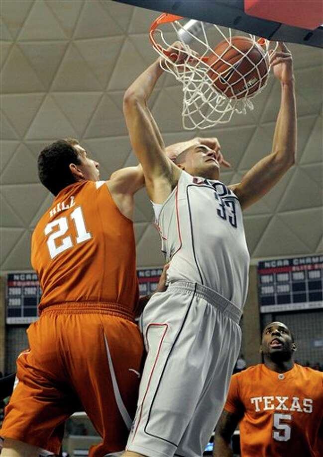 Texas's Matt Hill, left, fouls Connecticut's Gavin Edwards during the first half of their NCAA men's college basketball game in Storrs, Conn., on Saturday, Jan. 23, 2010. (AP Photo/Fred Beckham)