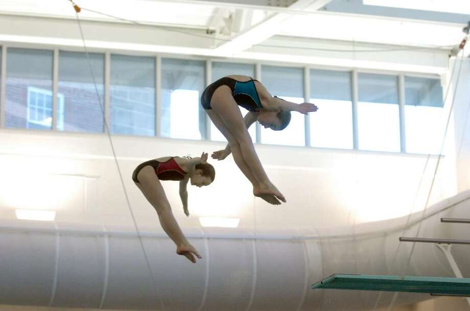 Rachel Burston, left, and Caleigh Kuppersmith dive during the CHAMPS Dive-a-thon on Saturday, January 23, 2010 in the Greenwich Family YMCA Natatorium.  Kirsten Parkinson, 14, organized a Dive-a-thon so she and her Marlin Dive Club teammates could raise money for CHAMPS (Children Against Mines Program) International, an initiative of the Marshall Legacy Institute that helps children who are victims of landmines. Photo: Keelin Daly / Greenwich Time