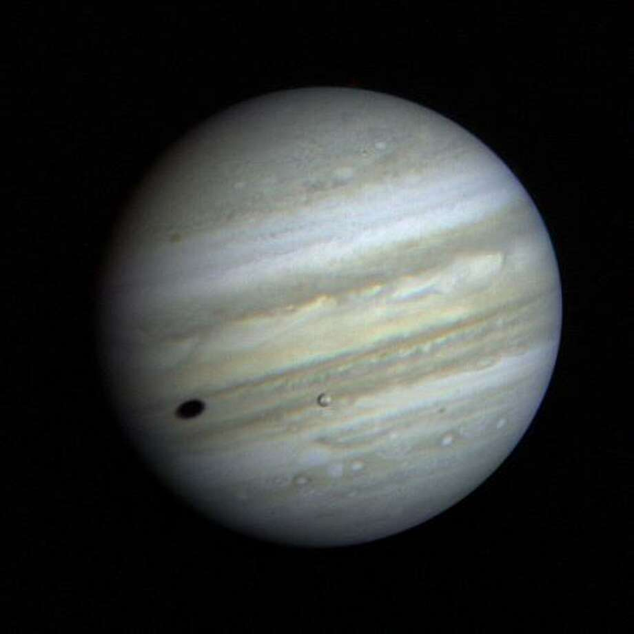 Jupiter's satellite Io poses before the giant planet in this photo returned January 17, 1979, from a distance of 29 million miles (47 million kilometers). The satellite's shadow can be seen falling on the face of Jupiter at left. Io is traveling from left to right in its one-and-three-quarter-day orbit around Jupiter. Even from this great distance the image of Io shows dark poles and a bright equatorial region. (Photo by NASA) Photo: NASA