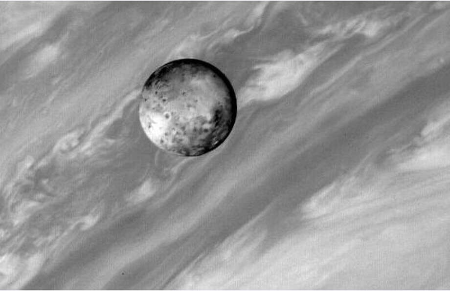 Twenty years ago this month, NASA's Voyager 1 spacecraft flew past Jupiter and its moons. This sharp picture of moon Io against a background of gas giant Jupiter's diffuse swirling cloud bands was recorded by Voyager's camera from a distance of about 5 million miles. Even this early image shows curious round features on Io's surface with dark centers and bright rims more than 40 miles across. Now known to be volcanic in origin, these features were then thought likely to be impact craters, commonly seen on rocky bodies throughout the Solar System. But as Voyager continued to approach Io, close-up pictures revealed a bizarre world devoid of impact craters, frequently resurfaced by volcanic activity. In fact, Io's volcanism is so intense that subsequent Voyager images produced an astounding discovery - the first observed extraterrestrial volcanic eruptions. (photo by NASA) Photo: NASA