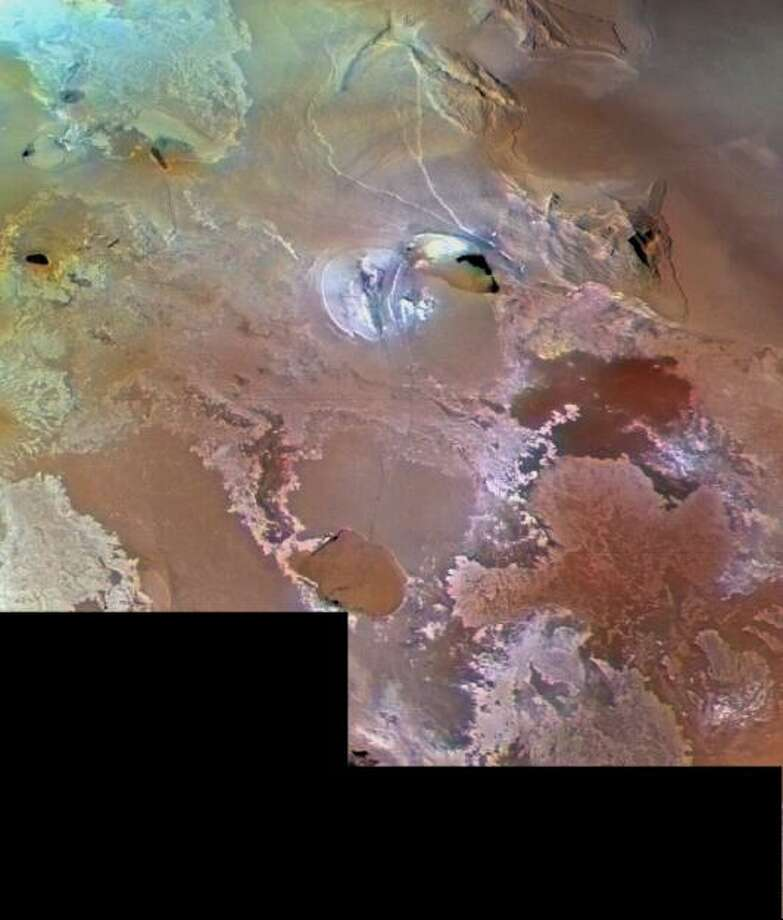 Io's volcanic plains are shown in this Voyager 1 image, which spans an area about 1030 km (640 miles) from left to right. North is about the 1:30 position. Numerous volcanic calderas and lava flows are visible here. The brown teardrop-shaped feature at left center is Galai Patera, a 100-km-long (62 mi) lava-flooded caldera (collapsed vent) of a volcano. The composition of Io's volcanic plains and lava flows has not been determined. The prevalent yellow, brown, and orange material may consist dominantly of sulfur with surface frosts of sulfur dioxide or of silicates (such as basalt) encrusted with sulfur and sulfur dioxide condensates. The whitish patches probably are freshly deposited SO2 frost. (Photo by NASA) Photo: NASA