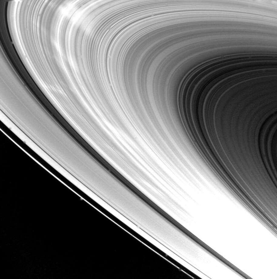 Eight hours after its closest approach to Saturn on Nov. 12, 1980, Voyager 1 took this picture of the planet's ring system. Major features of the rings are clearly seen: from the top of the image down is the bright F-ring, the A-ring, the Cassini Division, the broad B-ring, and the C-ring (dark gray area). The spacecraft took this picture at a distance of 720,000 kilometers (446,000 miles) from an angle approximately 30 degrees above the ring plane. The unique lighting in this view brings out the many hundreds of bright and dark ringlets that make up this very thin, phonograph record-like ring system. The dark spokelike features seen in images taken during approach to Saturn now appear as bright streaks, indicating that they possess a strong forward-scattering property. (Photo by NASA) Photo: NASA