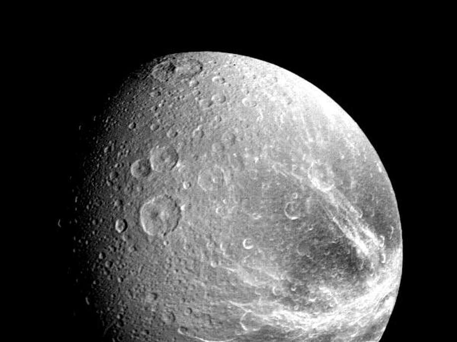 Many large impact craters are seen in this view of the Saturnian moon Dione taken by NASA's Voyager 1 on Nov. 12, 1980 from a range of about 240,000 kilometers (149,000 miles). Bright radiating patterns probably represent debris rays thrown out of impact craters; other bright areas may be topographic ridges and valleys. Also visible are irregular valleys that represent old fault troughs degraded by impacts. (Photo by NASA) Photo: NASA