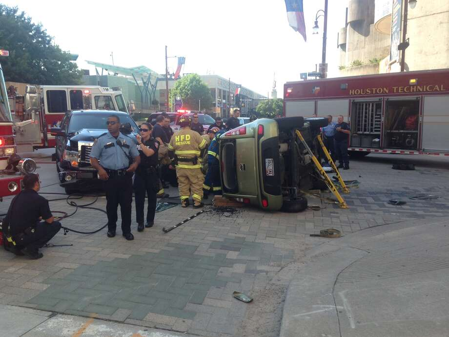An SUV flipped at the corner of Texas and Louisiana in downtown Houston.