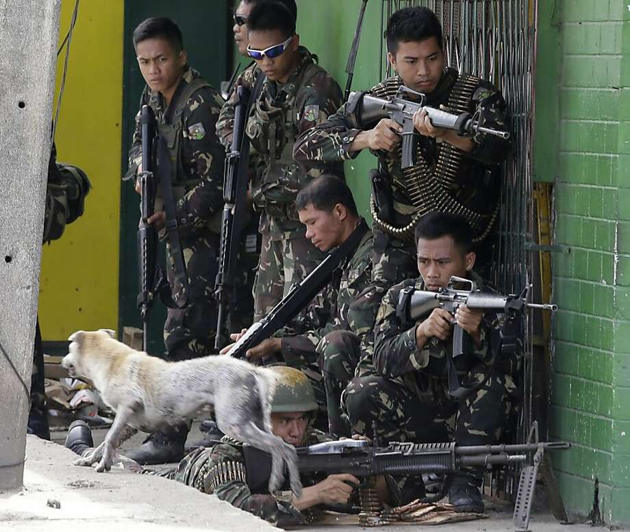 Don't shoot! Coming through!Government troops prepare to engage Muslim rebels holding scores of hostages as human shields for a fourth day in Zamboanga, Philippines. Photo: Bullit Marquez, Associated Press