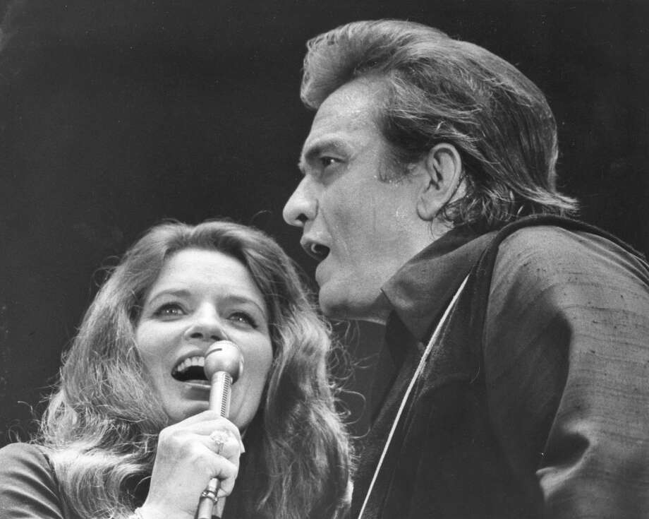 Johnny Cash and wife June Carter are shown during a performance at the Houston Livestock Show in 1971. They drew 160,475 persons for their six performances, 46,749 fewer than Elvis Presley drew for the comparable the previous year.  (Othell O. Owensby Jr. / Houston Chronicle) Photo: Othell O. Owensby Jr, © Houston Chronicle