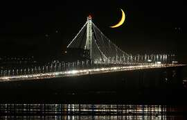 A crescent moon rises above the new tower of the Bay Bridge as seen on September 8, 2013 from Emeryville, Calif.