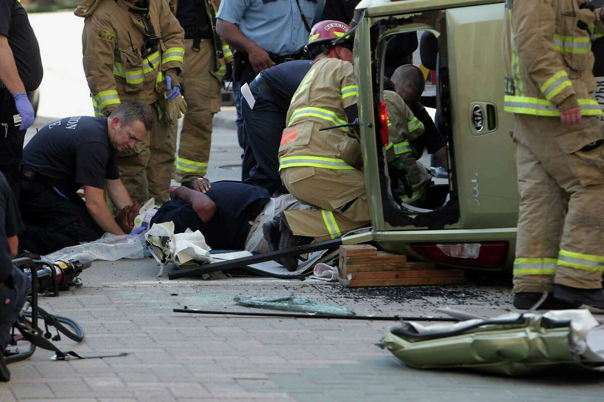 Houston Fire Department personnel work to extract the driver of an overturned vehicle at the scene of a two vehicle accident Thursday, Sept. 12, 2013, in Houston.