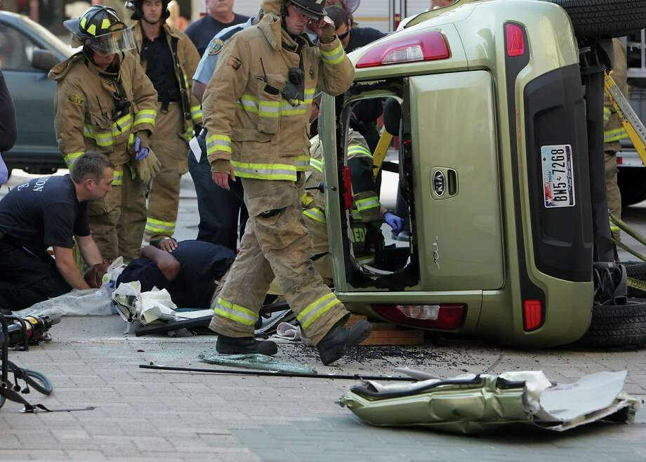Houston Fire Department personnel work to extract the driver of an overturned vehicle at the scene of a two vehicle accident Thursday, Sept. 12, 2013, in Houston. Photo: James Nielsen, Houston Chronicle / © 2013  Houston Chronicle