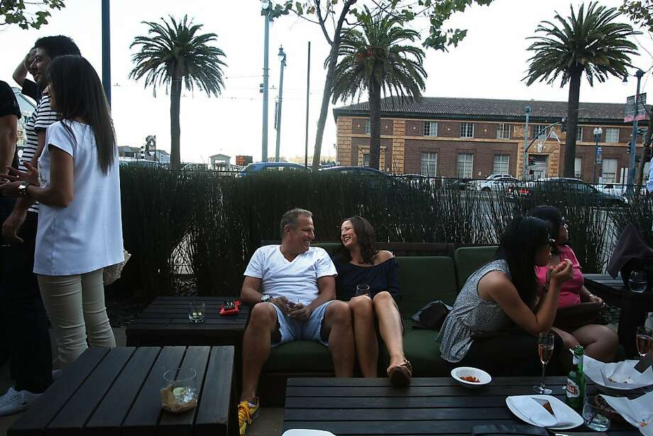 Rob Elliott and Tia Hartley (center) of Walnut Creek hang out at Americano, near the Ferry Building on the Embarcadero. It's so popular on some Friday nights at quitting time, that 600 people will flow in. Photo: Liz Hafalia, The Chronicle