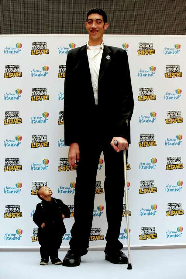 The world's tallest man, Sultan Kösen (R) standing at 8 ft 1 in (246.5 cm)  poses with shortest man in the world He Pingping standing at 2 ft 5.37 in (74.61 cm) during celebrate the launch of the Guinness World Records live roadshow in Istanbul, on January 14, 2010.  AFP PHOTO / MUSTAFA OZER Photo: MUSTAFA OZER, AFP/Getty Images / 2010 AFP