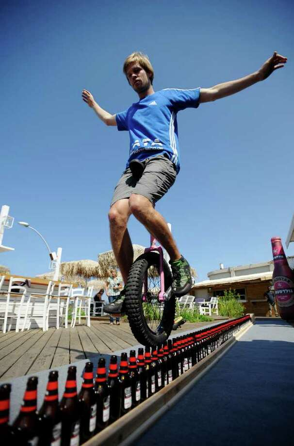 Lutz Eichholz, 25, from Germany, is seen during his attempt to set a new Guinness world record in riding a mono-cycle over bottles of beer in the city of Tel Aviv on September 26, 2011. He succeeded by riding a total length of 8.93 meters consisting of 127 bottles. The former record was 7.99 meters.  AFP PHOTO/DAVID BUIMOVITCH Photo: DAVID BUIMOVITCH, AFP/Getty Images / 2011 AFP