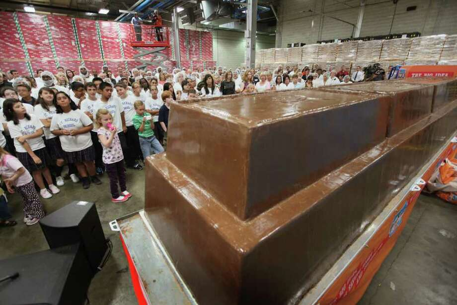 Workers and guests at the World's Finest Chocolate company look at a 12,290 pound chocolate bar they created to set a new Guinness World Record September 13, 2011 in Chicago, Illinois. The bar, which stands nearly 3 feet high and measures 21 feet long, beat the previous record chocolate bar by more than a ton. Photo: Scott Olson, Getty Images / 2011 Getty Images