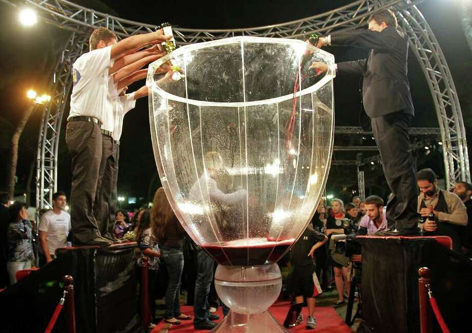 Lebanese men pour wine into a giant glass before Lebanon set a new Guinness world record for the largest wine glass, measuring 2.4m in height and 1.65m in width, in Beirut on October 29, 2010. Photo: ANWAR AMRO, AFP/Getty Images / 2010 AFP