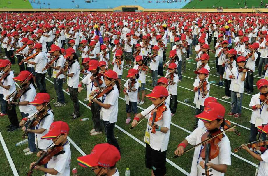 In this picture taken on September 17, 2011, local students from 170 schools play violins together in a Guinness World Record attempt for the most amount of people playing violins together at one time, at a stadium in central Changhua County. More than 4,600 Taiwanese schoolchildren came together for a mass violin-playing session on September 17, breaking a world record that had stood for 86 years. Photo: SAM YEH, AFP/Getty Images / 2011 AFP