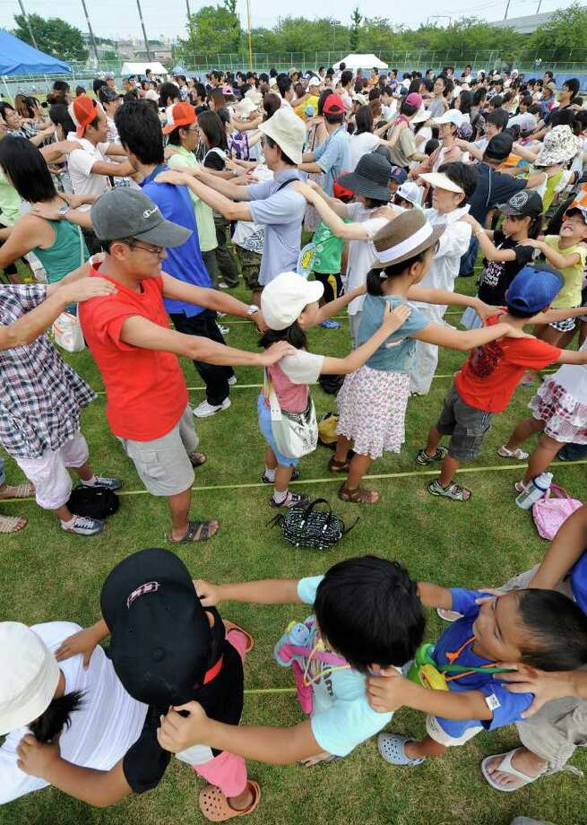 People line up and rub the shoulders of those in front in an effort to set a new world record for the 'longest massage chain' in Yachiyo, in suburban Tokyo, on August 21, 2010. The participants unfortunately failed to break the world record of 1,223 participants as recognized by the Guinness Book of Records. Photo: TORU YAMANAKA, AFP/Getty Images / 2010 AFP
