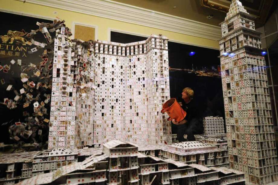 "US ""cardstacker"" Bryan Berg knocks down his Guinness World Record for the largest house of freestanding playing cards, a replica of the Venetian Macao, the Plaza and Sands Macao casino and hotel buildings in Macau on March 20, 2010. Berg's promotional attempt took 44 days and used a total of 218,792 playing cards. Photo: DALE DE LA REY, AFP/Getty Images / 2010 AFP"