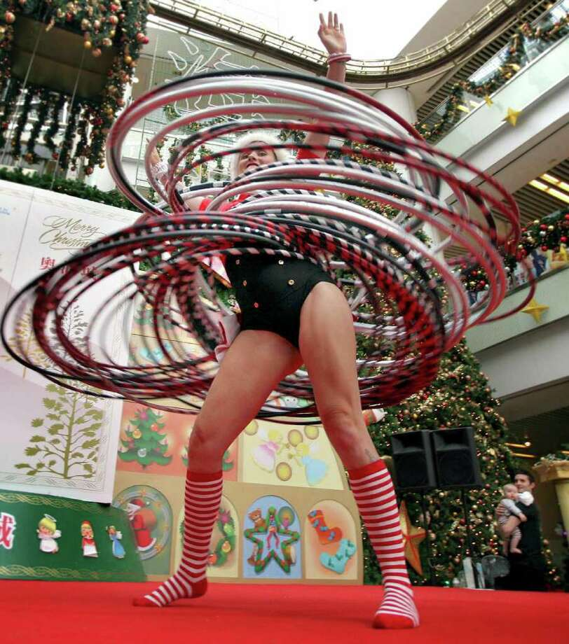 Hong Kong, CHINA:  The Guinness World Record Champion of Hula Hoops, Kareena Oates from Australia, performs her hula-hoops skills at a local shopping mall, in Hong Kong, 22 December 2006.  Oates manipulates about 70 hula-hoops around her body at one time, and will be shown to the public during the X'mas period until 26 December. Photo: SAMANTHA SIN, AFP/Getty Images / 2006 AFP