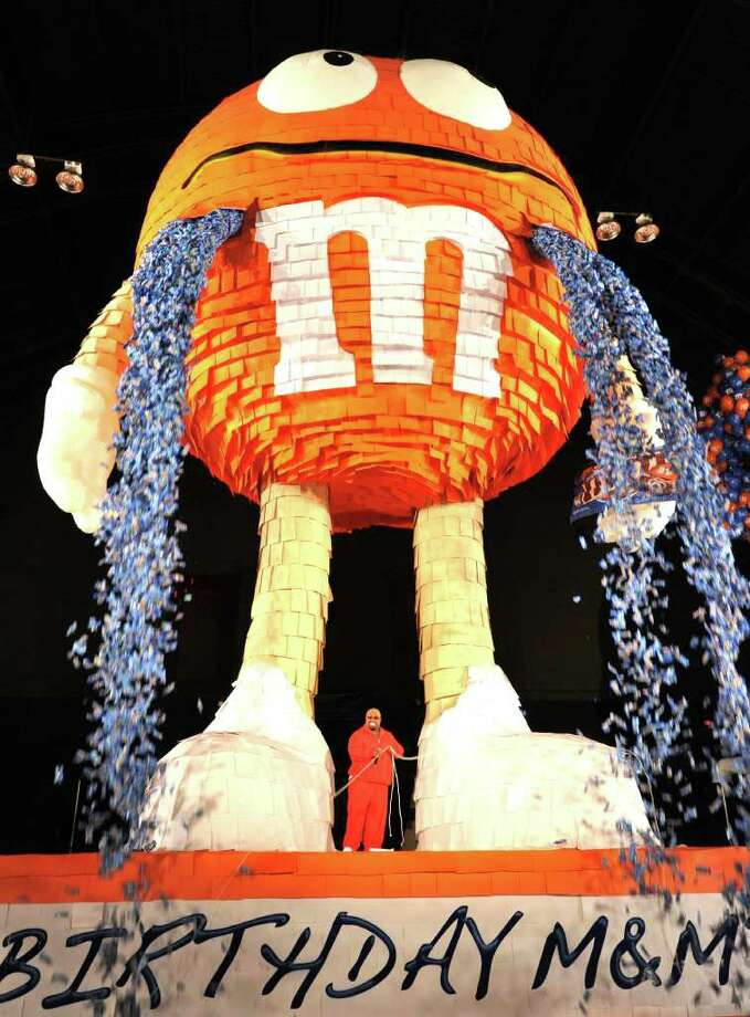 Singer Cee Lo Green (C) pulls ropes letting thousands of M&M's Pretzel packages to fall from at 46 foot (14 meter) piñata August 4, 2011 in New York. M&M's used the promotion to break a new Guinness Record for world's largest piñata. Photo: STAN HONDA, AFP/Getty Images / 2011 AFP