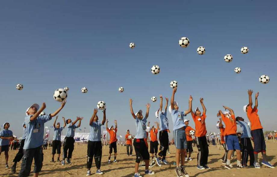 Thousands of Palestinian children throw footballs in the air during an attempt to set a new Guinness world record of 2,011 footballs bounced simultaneously in an event organised by the the United Nations Relief and Works Agency (UNRWA) in the southern Gaza Strip town of Rafah on July 14, 2011. Photo: SAID KHATIB, AFP/Getty Images / 2011 AFP