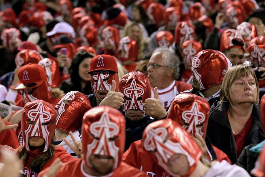 "Fans wear wrestling masks given away as a promotion as they set a Guinness World Record for ""largest gathering of people wearing costume masks"" during the game between the Chicago White Sox and the Los Angeles Angels of Anaheim on May 10, 2011 at Angel Stadium in Anaheim, California. Photo: Getty Images"