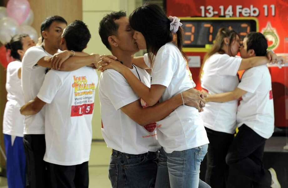 "Thai couples kiss during a competition for the ""World's Longest Continous Kiss"" to mark Valentine's Day in the Thai resort area of Pattaya on February 13, 2011. Fourteen couples took part in the kissing marathon in the hope of breaking the Guinness world record, and in the process to receive prizes totalling more than 200,000 Thai baht (6,666 USD) and a diamond ring. Photo: PORNCHAI KITTIWONGSAKUL, AFP/Getty Images / 2011 AFP"