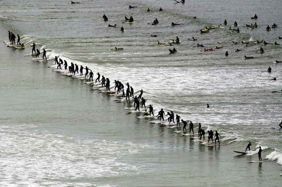 Surfers ride a wave in the annual Earthwave event, where the participating surfers try to break the Guinness World Record for the number of surfers surfing a single wave on September 26, 2010 at the Muizemberg beach on the outskirts of Cape Town, South Africa. Unconfirmed reports are that 95 surfers simultaneously rode a wave together, not enough to break the record of 103, set the previous year, at the same beach. Photo: RODGER BOSCH, AFP/Getty Images / 2010 AFP