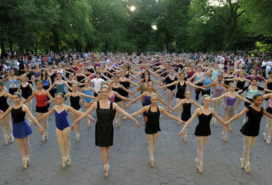 """Ballet dancers from all over the country join together at the Bandshell in New York's Central Park on August 2, 2010 and stand en pointe for one minute in an attempt to enter the Guinness Book of Records for """"Most Ballerinas En Pointe"""". Some 230 dancers set a record of 1 minute and 7 seconds and will be entered in the book. Photo: TIMOTHY A. CLARY, AFP/Getty Images / 2010 AFP"""