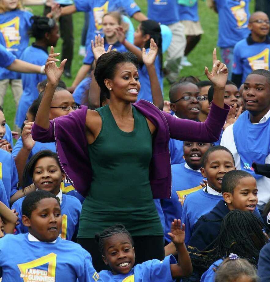 First lady Michelle Obama does jumping jacks with 400 school children on the South Lawn of the White House, on October 11, 2011 in Washington, DC. First lady Michelle Obama led local school children in doing one minute of continuous jumping jacks while attempting to help break the Guinness world record. Photo: Mark Wilson, Getty Images / 2011 Getty Images