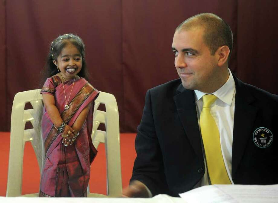 "Guinness World Records adjudicator Rob Molloy and Jyoti Amge (L), 18, attend a news conference in Nagpur on December 16, 2011. Amge was officially announced by the Guinness World Records on December 16 the world's ""shortest woman living (mobile)"" measured as 62.8cm (24.7 inches) and will take the title from US woman Bridgette Jordan, previously held the record at 69.5 cm (27.4 in). Photo: PUNIT PARANJPE, AFP/Getty Images / 2011 AFP"