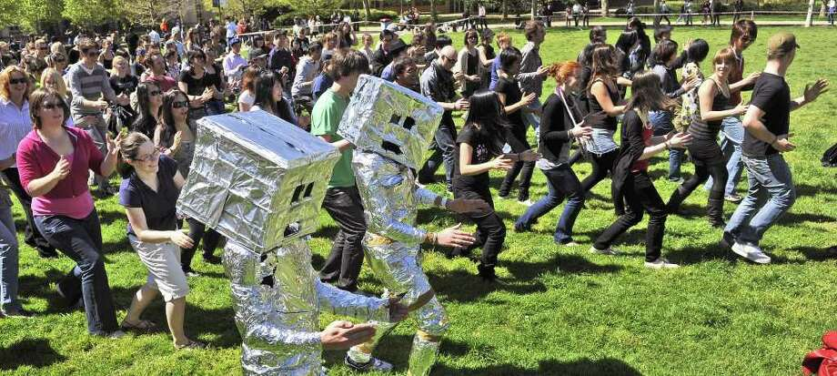 379 people, some dressed as robots, smash the offical Guinness World Record attempt for robot dancing at the University of Melbourne, on September 29, 2009, breaking the previous record of 279 people set by the University of Kent in England.  The robotic macarena was organised by Robogals, a non-profit group of young engineering undergraduates teaching robotics to schoolgirls to lift the profile of science in schools. Photo: WILLIAM WEST, AFP/Getty Images / 2009 AFP