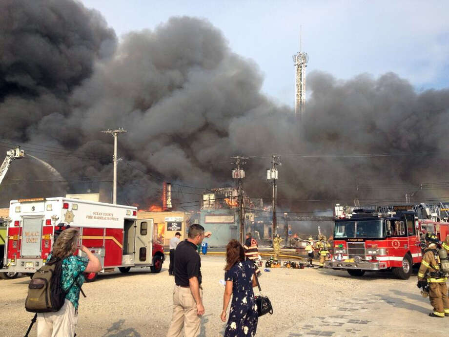 Firefighters battle a raging fire on the boardwalk in Seaside Heights, N.J. that apparently started in an ice cream shop and has spread several blocks down, Thursday, Sept. 12, 2013. The boardwalk was damaged in Superstorm Sandy and was being repaired.   MANDATORY CREDIT: PAPER AND PHOTOGRAPHER; Photo: The Asbury Park Press, Erik Larsen