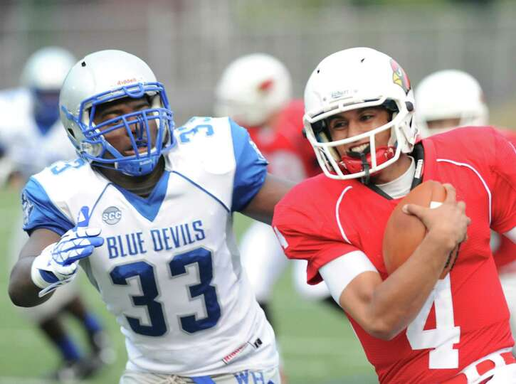 At right, Greenwich quarterback Jose Melo, # 4, runs the ball as West Haven's Tayvon Gibbs, # 33,  g
