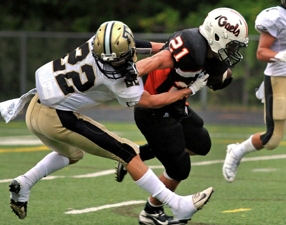 Shelton's Jason Thompson carries the ball to the endzone for a touchdown as he tries to shake Trumbull's Liam Moore, left, during high school football action in Shelton, Conn. on Thursday September 12, 2013. Photo: Christian Abraham / Connecticut Post