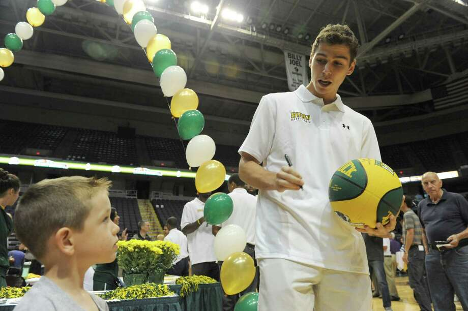Siena junior guard Rob Poole, left, signs a basketball for 4-year-old Brennan Thomas of Latham during Siena's annual Sneak Preview, where fans get to meet and greet the men's and women's teams at the Times Union Center on Thursday Sept. 12, 2013 in Albany N.Y. (Michael P. Farrell/Times Union) Photo: Michael P. Farrell / 00023841A