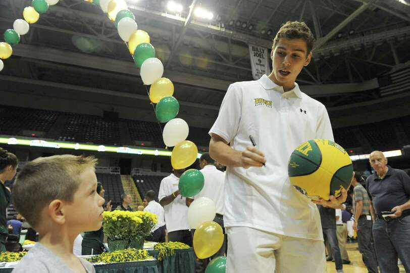 Siena junior guard Rob Poole, left, signs a basketball for 4-year-old Brennan Thomas of Latham durin