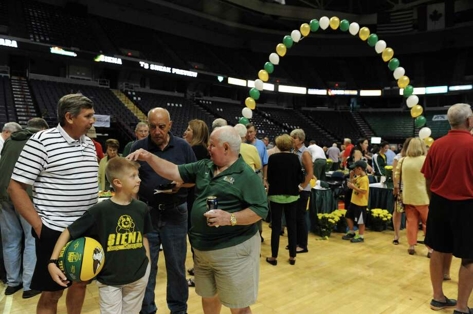 Siena alumni and fans enjoy socializing and snacks during Siena's annual Sneak Preview, where fans get to meet and greet the men's and women's teams at the Times Union Center on Thursday Sept. 12, 2013 in Albany N.Y. (Michael P. Farrell/Times Union) Photo: Michael P. Farrell / 00023841A